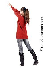 Back view of young brunette woman pointing at wall .
