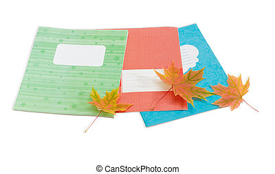 Several school exercise book and yellowed maple leaves -...