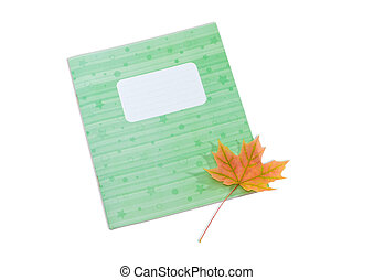 School exercise book and yellowed maple leaf on light...