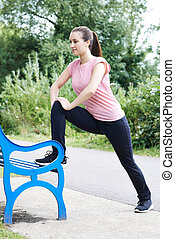 Woman Doing Stretches Using Park Bench