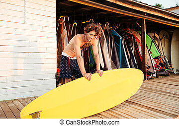 Professional young surfer getting surf board ready and...