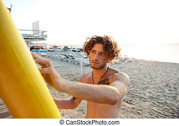 Professional young surfer getting board ready for surf at...