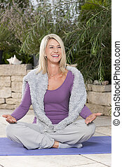 Happy matured woman doing yoga outdoor on the terrace