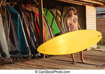 Young smiling professional surfer holding surf board at the...