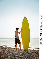 Man with his surfboard standing on the beach and looking at...