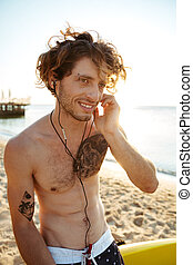 Close up portrait of a surfer listening music at beach -...