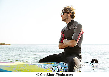Surfer sitting on surf board with hands crossed in ocean -...