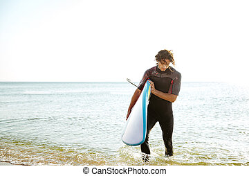 Man in swimsuit walking out of the water with surfboard -...