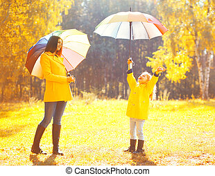 Moment of happiness Happy family with umbrellas in sunny...