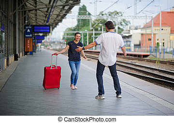 At an empty platform flee a young woman with red suitcase. -...