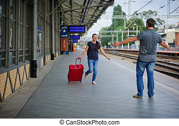 At an empty platform flee young woman with a red suitcase. -...