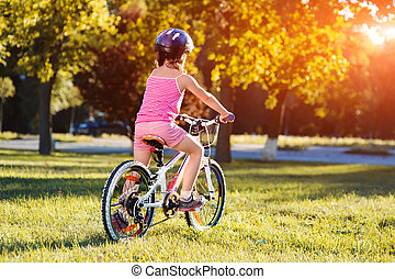 child girl riding bicycle on summer sunset in the park. -...