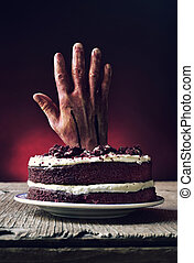 cake topped with a bloody hand in a scary scene for...