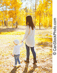 Mother walking with child in warm sunny autumn day