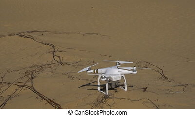 Quadrocopters takes off from the sand in the desert. Slow...