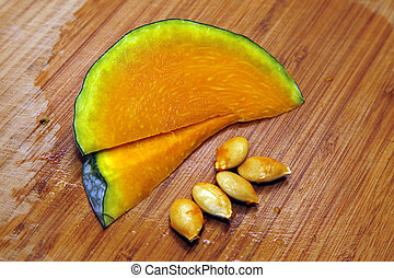 Slices of honeydew pumpkin on a wooden background