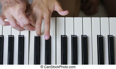 Woman teaching little girl to play the piano. musical...