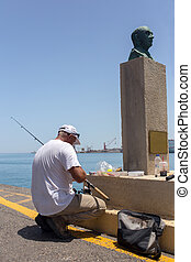 A grown man fishes on the pier