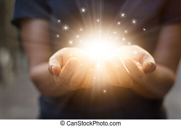 Stardust and magic in woman hands on dark background
