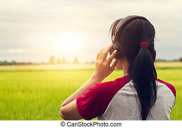 Freedom woman enjoying music with headphones outdoors