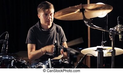 male musician playing drums and cymbals at concert - music,...