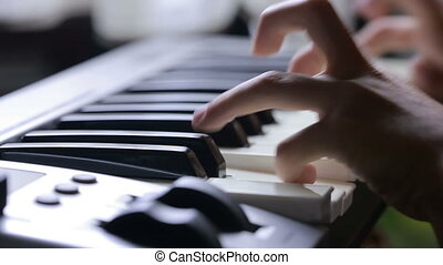 the hand on piano key in close-up shot. child learning to...