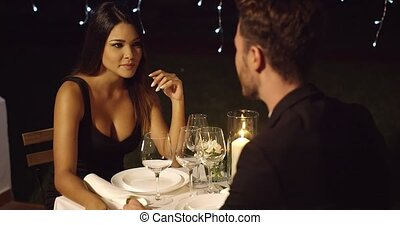 Beautiful long haired woman has dinner with man at fancy...