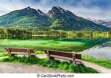Two wooden bench at the Hintersee lake in the Alps