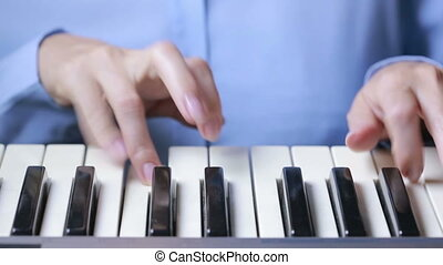 Woman hand playing a MIDI controller keyboard synthesizer...