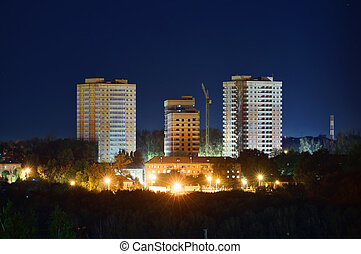 Construction of residental buildings at night - View on...