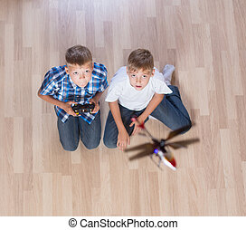 boys playing with flying helicopter model at home using...
