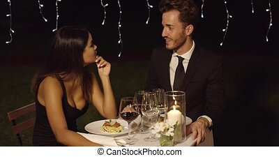 Handsome couple laughing while at restaurant during night...