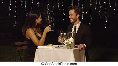 Romantic couple dining in an elegant restaurant raising...