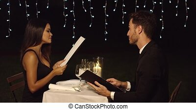 Young romantic couple reading the menu to order their food...