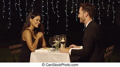 Couple smiles across restaurant dinner table while eating...