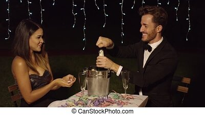 Man in suit and bow tie celebrates with date with champagne...