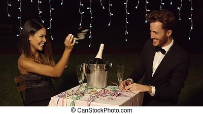 Couple celebrates with champagne in bucket and pastel...
