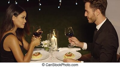 Young couple sipping red wine during dinner - Elegant...