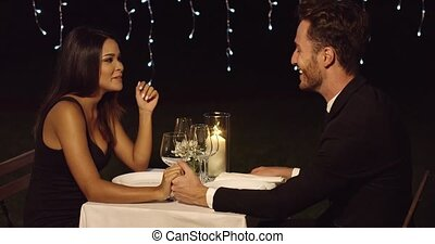 Loving young couple enjoy a romantic dinner seated at a...