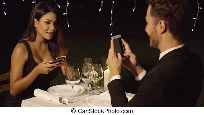 Man in suit takes photo of beautiful dinner date from across...