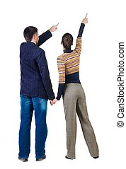 Young couple pointing at wall. Rear view. Isolated over...