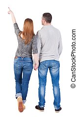young couple pointing at wal Back view (woman and man). . -...