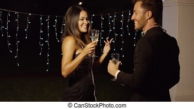 Handsome couple flirts with champagne in hand while standing...