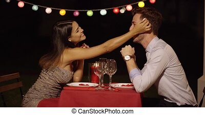 Couple holds hands across table and smiles while casually...