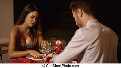 Beautiful woman in deep thought across table from handsome...