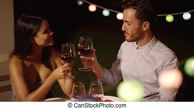 Romantic young couple enjoying dinner and wine at a...