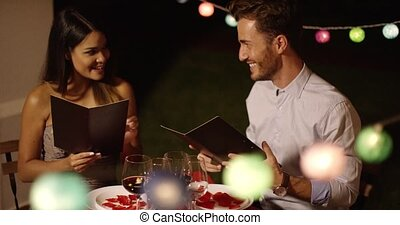 Young couple laughing as they go through the menu at a...