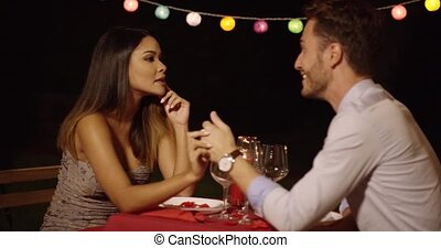 Man gestures at date across red covered table while at...