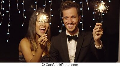 Young couple celebrating new year with sparklers - Elegant...