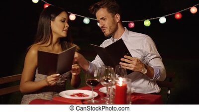 Loving young couple choosing food off a menu as they enjoy a...